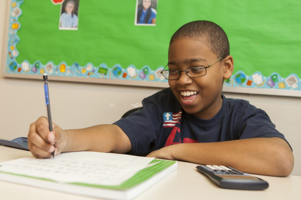 Smiling student writing at his desk