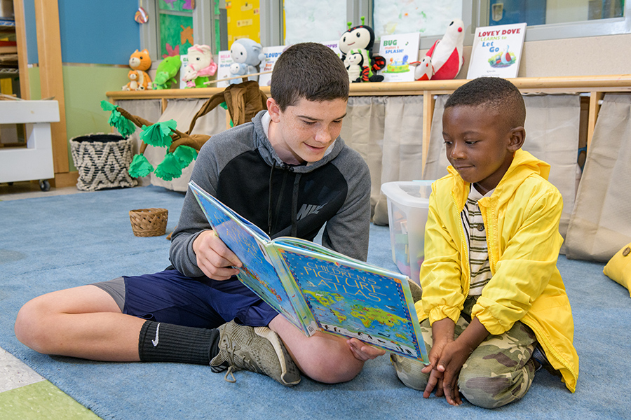 UD student helps child read a book at The College School