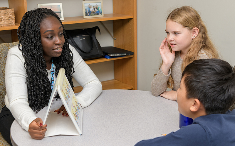 University of Delaware graduate student works with two students at The College School